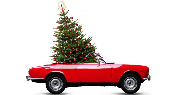 Red convertible carrying Christmas Tree
